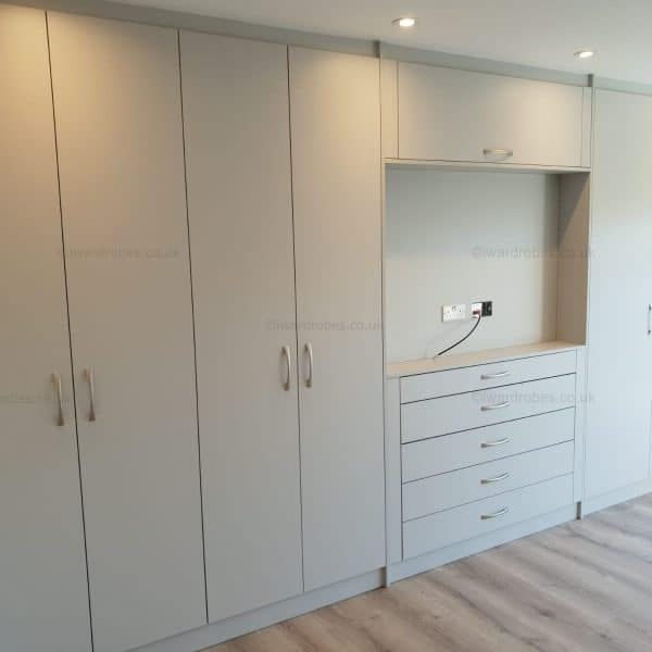 Fitted white wardrobe with hinged doors and TV niche